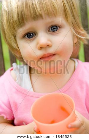 Curious Girl Toddler With Gorgeous Blue Eyes, Holding An Orange Plastic Cup, On Outdoor Setting.