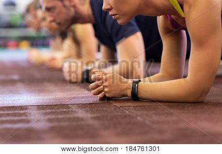 poster of fitness, sport, exercising, training and healthy lifestyle concept - group of people doing plank exe