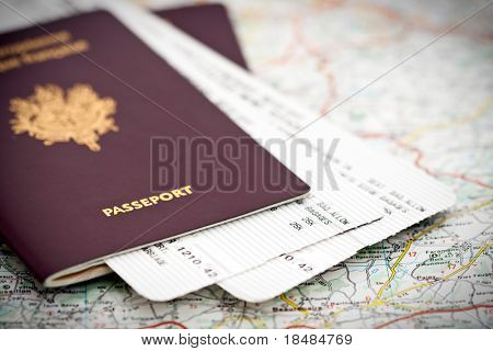 Passport book and tickets on a road map