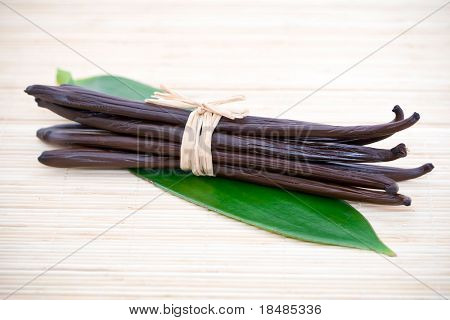 Bundle of vanilla bean pods on green leaf and bamboo mat.
