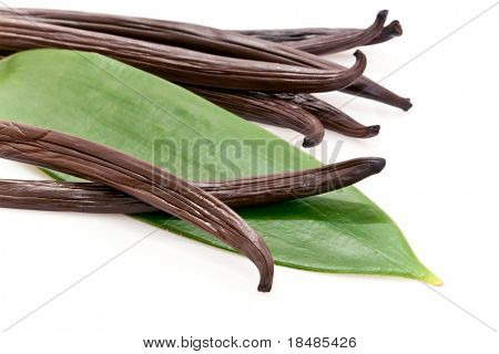 Fresh vanilla pods with a green leaf.