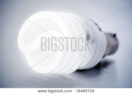 A CFL light bulb on grey background