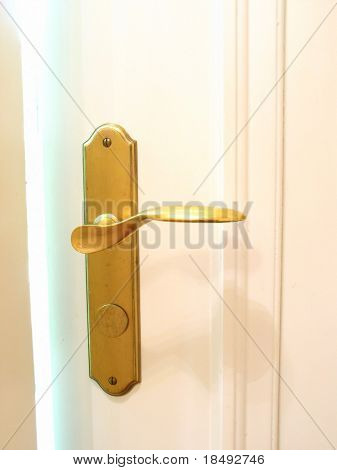 Golden door handle with bright hazy light streaming from door crack