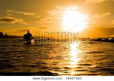 Sunset over ocean with surfers
