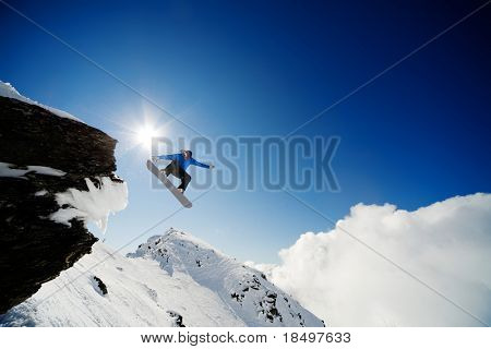 Snowboarder jumping through air after rock drop
