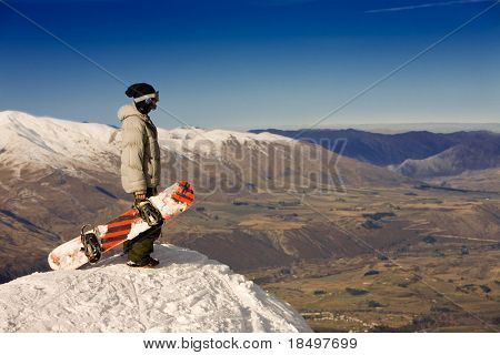 A snowboarder stands on a peak over looking a spectacular view