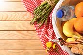 Picnic Wicker Basket With Food On Wood Table Top poster