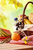 Picnic Wicker Basket With Food On Table In Field Vertical poster