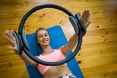 Smiling fit woman exercising with pilates ring on mat in fitness studio poster