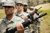 Group of military soldiers standing with rifles at boot camp poster