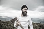 Bearded Man, Holds Axe On Mountain Top With Cloudy Sky poster