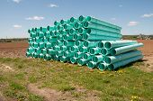 stock photo of pipefitter  - pile of sewer piping stacked by a field - JPG