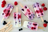 Healthy Mixed Berry Yogurt Popsicles With Fruit On A White Marble Background poster