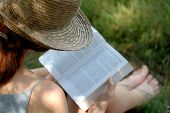 pic of girl reading book  - Closeup of woman reading book at the grass - JPG