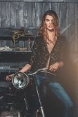 Sexy Biker In Erotic Shirt And Jeans Standing At Motorcycle poster