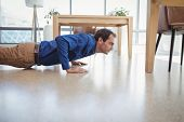 Determined executive doing push-ups in office poster
