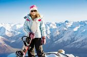 Woman holding snowboard with mountains in background