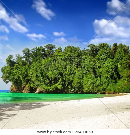 Beautiful tropical paradise with blue sky, green brush, white sands, and emerald waters