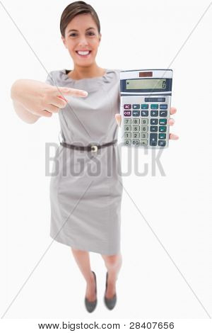 Woman pointing at hand calculator against a white background