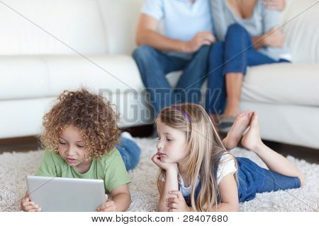 Children using a tablet computer while their parents are watching in their living room