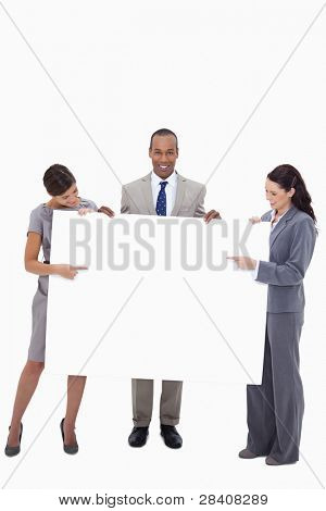 Businesspeople pointing at blank sign in their hands against a white background