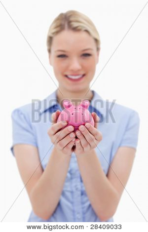 Piggy bank being held by young woman against a white background