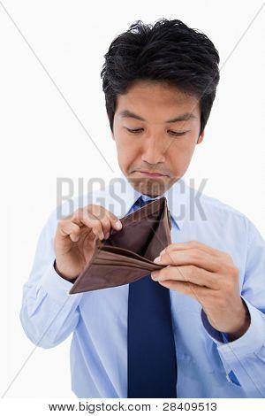 Portrait of a sad businessman showing his empty wallet against a white background