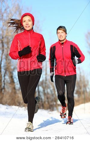 Sport couple running in winter snow. Woman and man runners jogging outdoors. Healthy fitness lifestyle concept with happy smiling young multiracial couple.