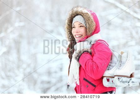 ice skating winter woman holding ice skates outdoors in snow. Beautiful young mixed race chinese asian / caucasian woman