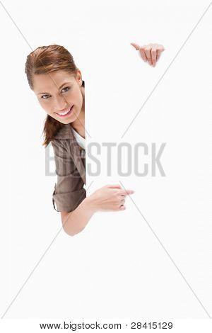 Smiling woman pointing around blank sign against a white background