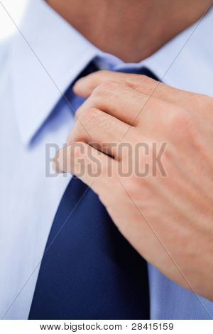 Close up of a businessman fixing his tie against a white background