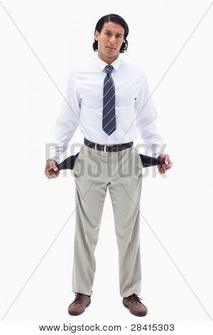 Portrait of a broke businessman showing his empty pockets against a white background