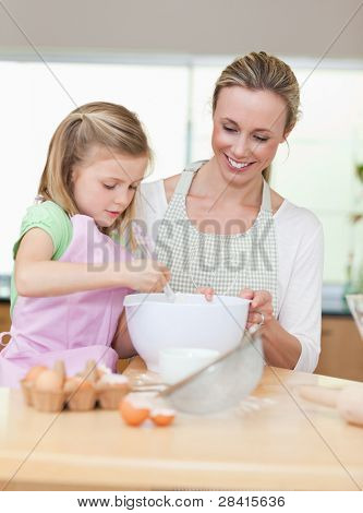 Smiling mother and daughter preparing dough for cookies togehter