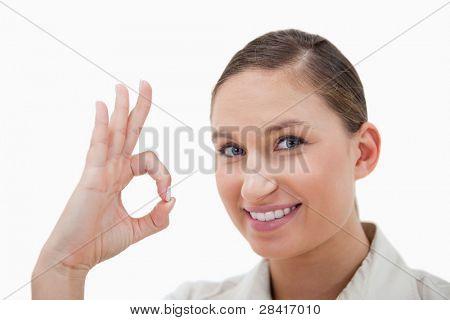 geschäftsfrau Unterzeichnung, dass alles in Ordnung vor einem weißen Hintergrund ist