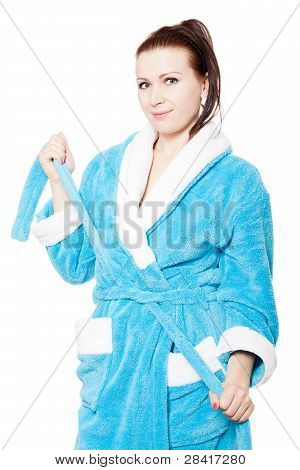 Young Woman In Blue Bathrobe Ties Waistband In A Bungle Against White Background