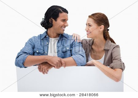Smiling couple leaning on blank wall against a white background