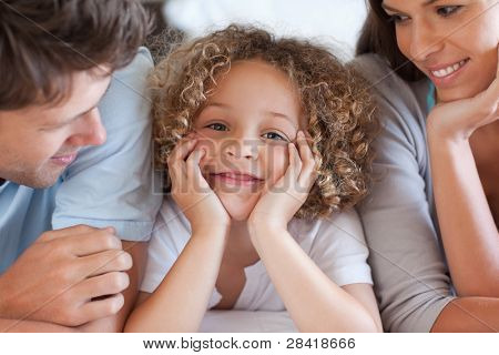 Close up of parents looking at their son while lying on a bed
