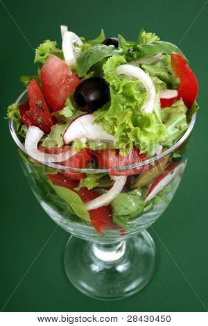 Fresh salad with onion, tomato and basil on black