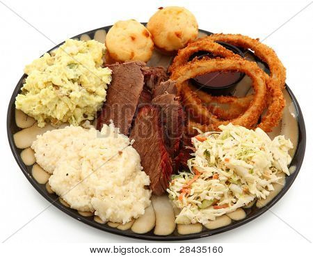 Beef brisket, grits, potato salad, cole slaw, onion rings, bbq sauce, corn muffins in a plate over white.