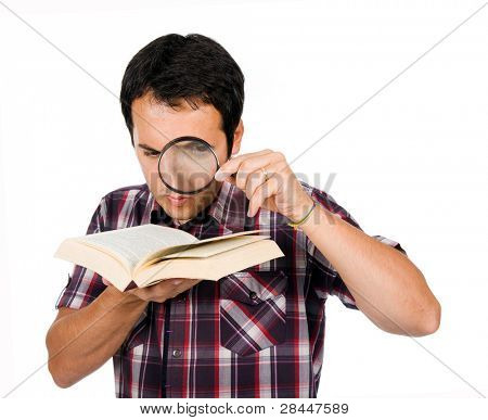 Young man reading a interesting book with magnifying glass, isolated on white
