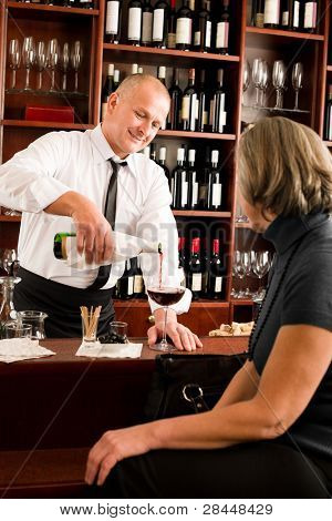Wine bar professional waiter serve glass senior woman smiling