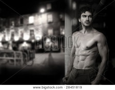 Fine art black and white photo of a young muscular sultry sexy male model