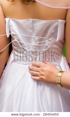 mother tightening a corset on her daughter's wedding dress
