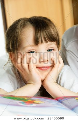 adorable little girl reading a book on the bed at home