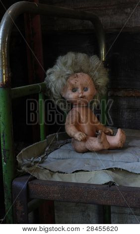 pour childhood, old dirty doll sitting on the old bed