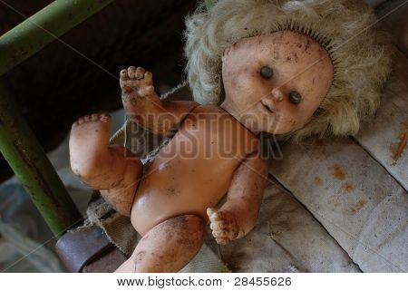 picture of poverty, old dirty doll on the rusty iron bed with an old dirty mattress