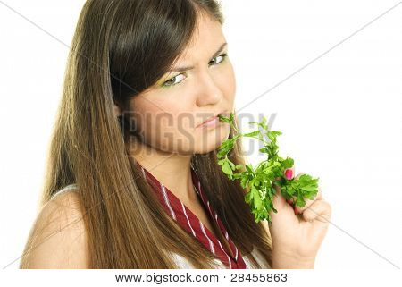 portrait of an unhappy beautiful brunette girl eating fresh green parsley