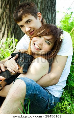 happy couple spending time in summer park with their puppy