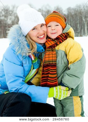 happy young mother and her little son spending time outdoor in winter park