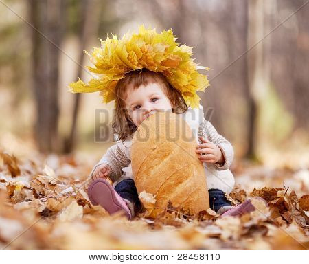 cute baby girl having a picnic, sitting on the grass in the autumn park and eating a long loaf
